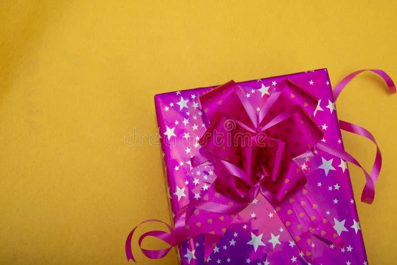 黄色背景上的粉红色圣诞礼物盒,复制空间横幅 库存照片