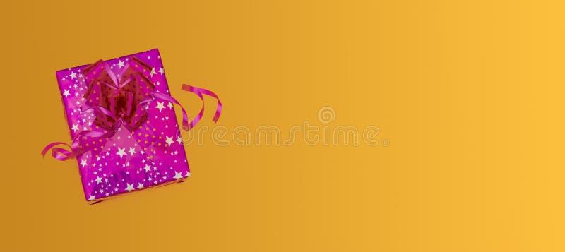 黄色背景上的粉红色圣诞礼物盒,复制空间横幅 免版税库存照片