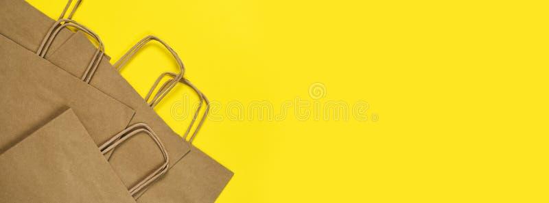 黄色背景下购物的手工纸袋 平的 礼品袋 免版税图库摄影