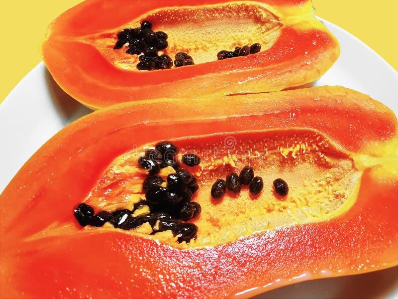 黄色背景中半隔的橙色熟木瓜切口 免版税库存照片