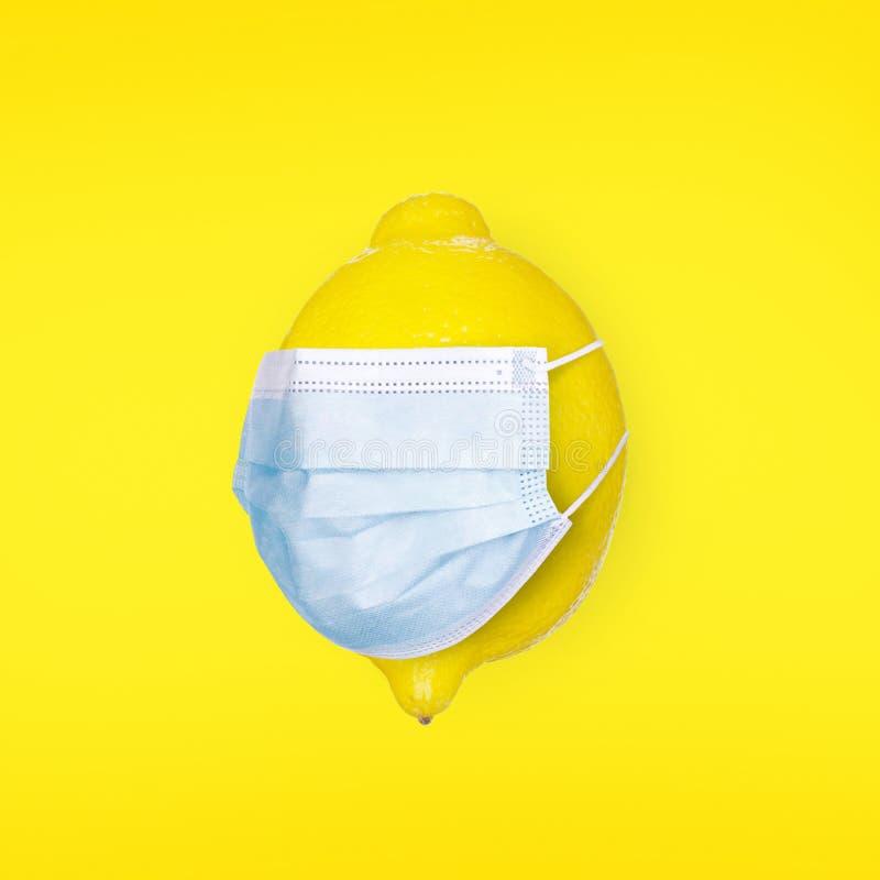 黄色背景中带医用口罩的柠檬 保护和预防病毒和疾病的概念 冠状病毒 库存照片