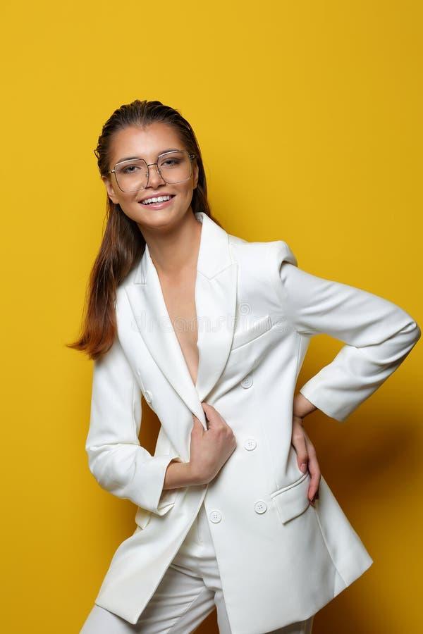 黄色背景中戴眼镜的优雅年轻女子 免版税库存照片