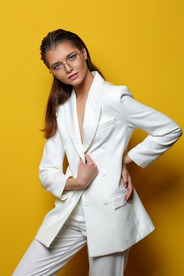 黄色背景中戴眼镜的优雅年轻女子 免版税库存图片