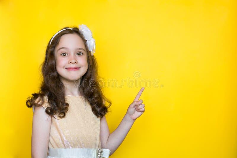 黄色背景点的愉快的女孩她的在空间的手指在上写字的 r 库存照片