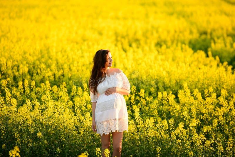 黄色背景的怀孕的女孩 看看他的胃,想象他的未出生的孩子 o 免版税图库摄影