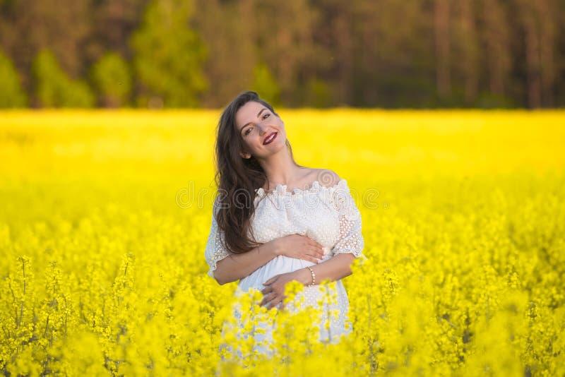 黄色背景的怀孕的女孩 看看他的胃,想象他的未出生的孩子 o 免版税库存图片
