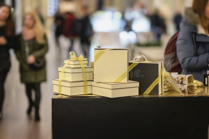 黄色节日礼物箱子栓与丝带,礼品包装材料在商店窗口,购物的画廊,被弄脏的走的人民 免版税库存图片