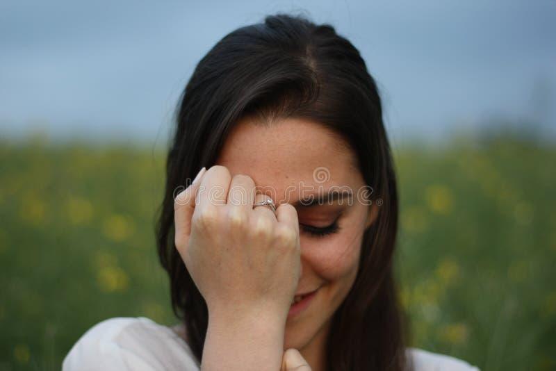 黄色花田的美女与黑暗的多云天空陈列定婚戒指 库存图片