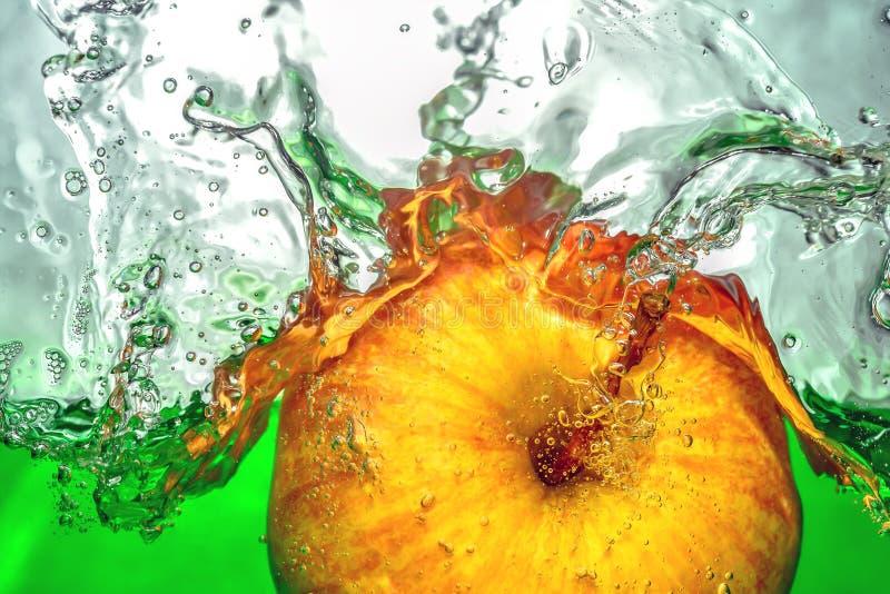 黄色苹果移动绿色水飞溅和下落 免版税库存照片
