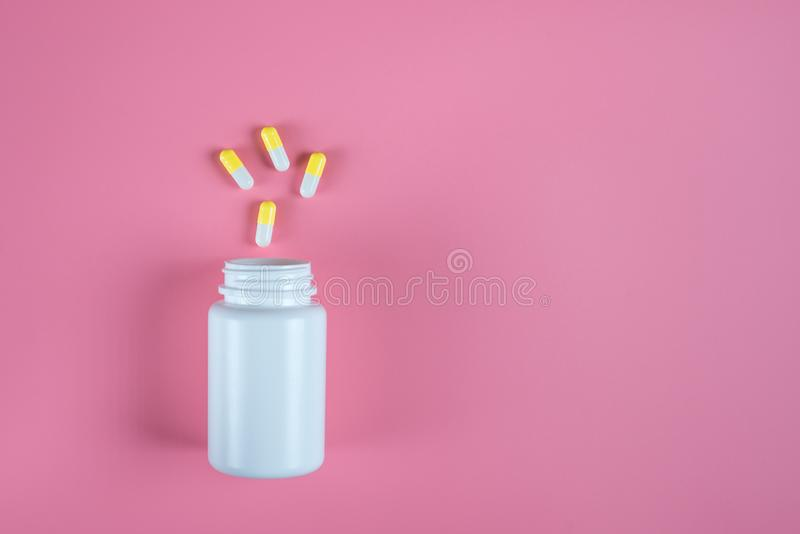 黄色药片、片剂和白色瓶在桃红色背景 免版税库存照片