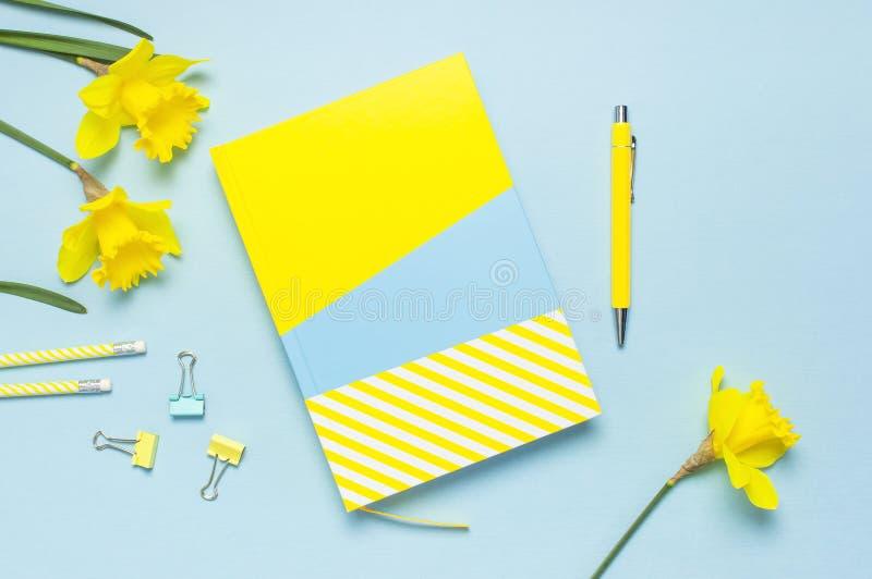 黄色蓝色笔记本,笔,夹子,春天花在蓝色背景的黄水仙水仙 女性桌面,办公桌,春天 免版税库存图片