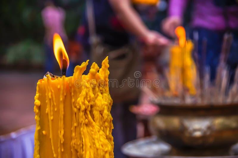 黄色蜡烛和香火有迷离背景 库存照片