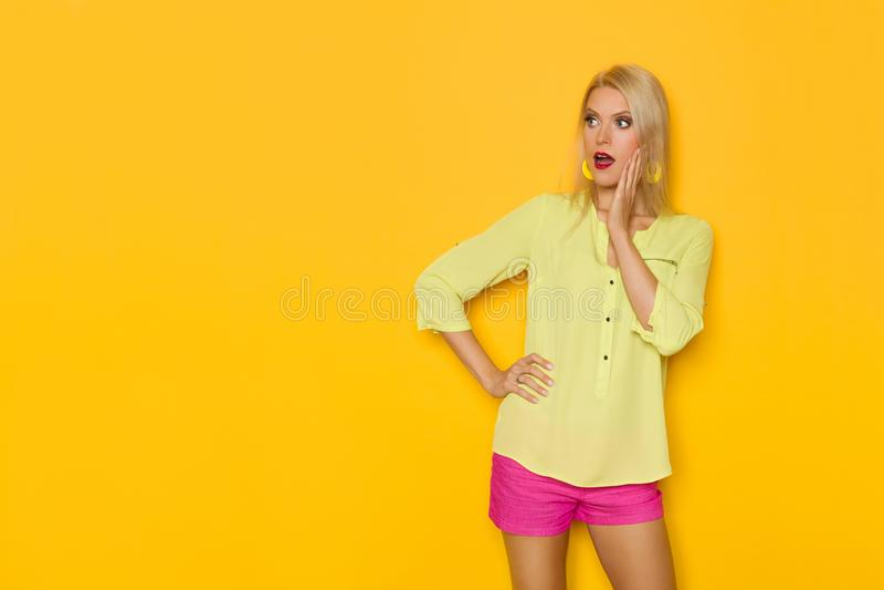 黄色衬衣和桃红色短裤的惊奇的美丽的白肤金发的妇女握在下巴的手并且看  图库摄影