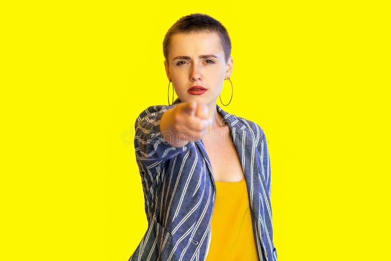 ?? 黄色衬衣和镶边衣服身分的,看和指向的严肃的年轻短发美女画象 库存图片