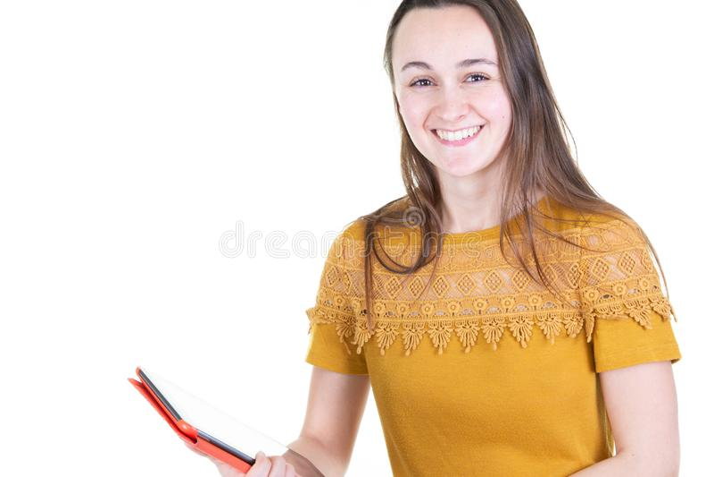 黄色衬衣的激动的女孩使用在白色背景有平板电脑的片剂微笑的妇女隔绝的 库存图片