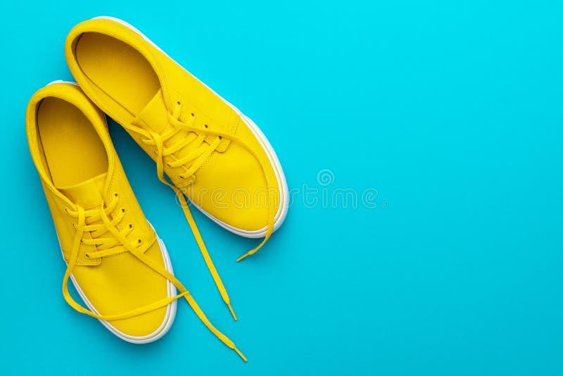 黄色被解开的运动鞋顶视图在蓝色绿松石背景的与拷贝空间 库存图片
