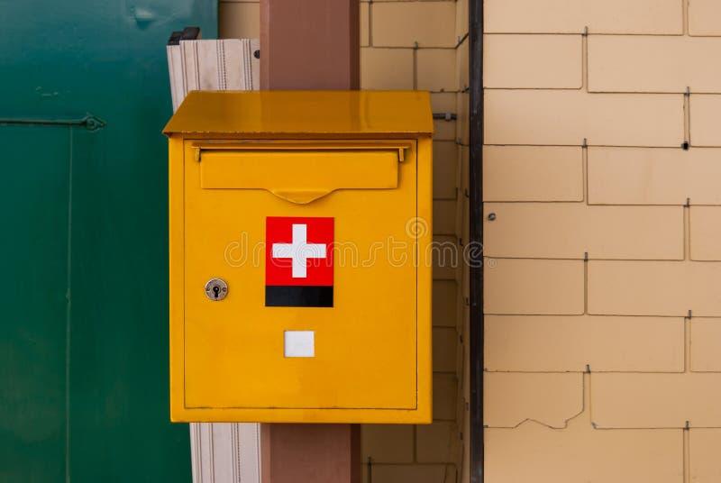 黄色邮箱瑞士邮政局在砖墙登上了 免版税库存图片