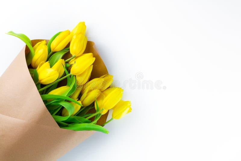 黄色郁金香花束在牛皮纸包裹的在白色背景,国际妇女的天贺卡的 库存图片