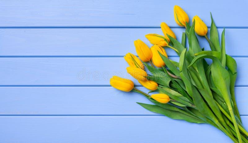 黄色郁金香花束在蓝色木板桌上的  免版税图库摄影