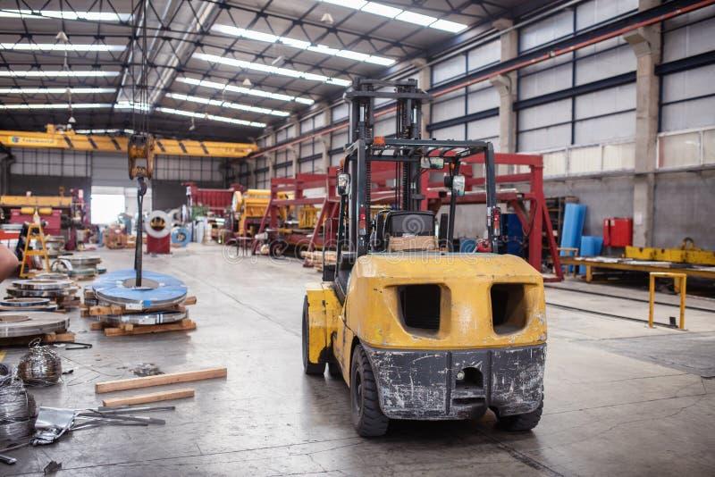 黄色铲车在仓库里准备好运输 库存照片