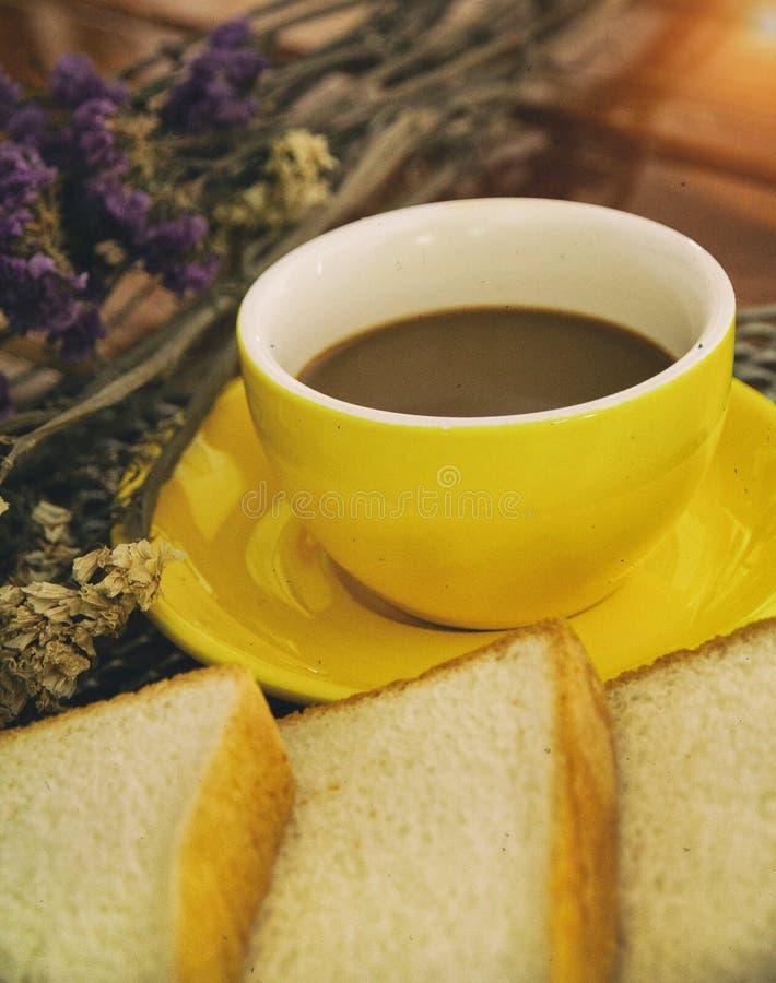黄色陶瓷咖啡杯抽象派设计背景在切的面包、葡萄酒和艺术样式,温暖的轻的口气旁边投入了 库存照片