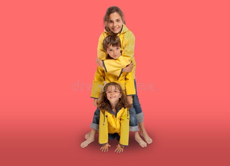 黄色雨衣的三年轻兄弟姐妹 免版税库存照片