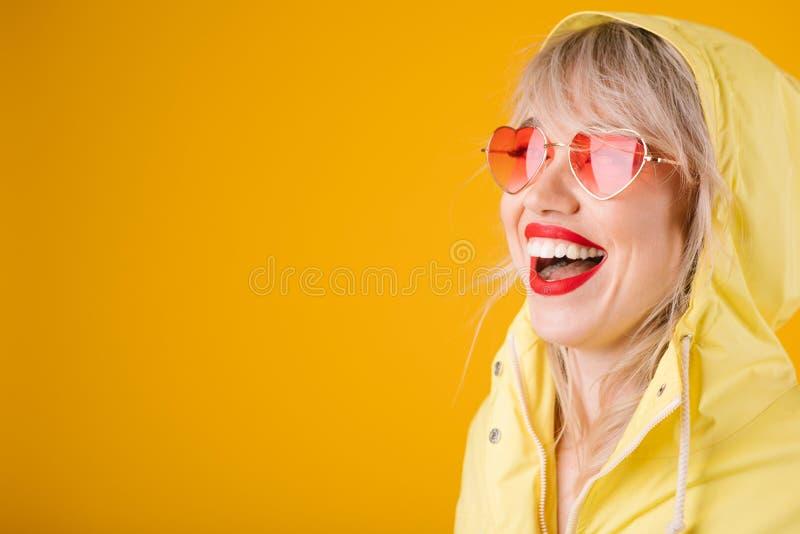 黄色雨衣 黄色背景witn桃红色心形的太阳镜的愉快的笑的妇女 明亮的情感 免版税图库摄影