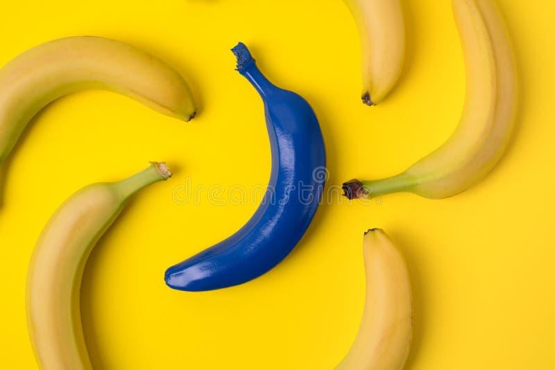 黄色香蕉和一蓝色在黄色背景 库存照片