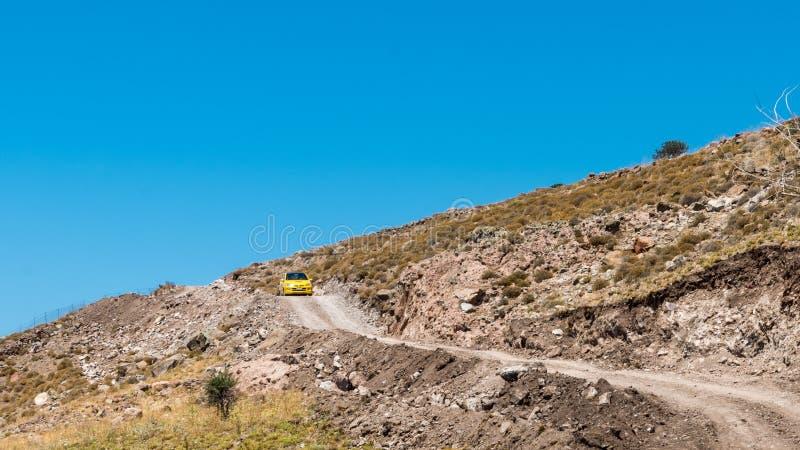 黄色驾车在贫瘠岩石山路下 图库摄影