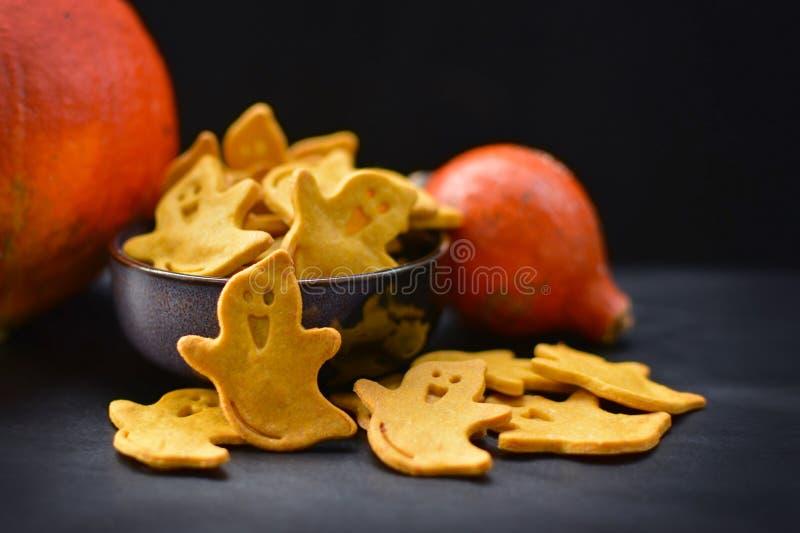 黄色鬼的鬼魂塑造了万圣节曲奇饼用在黑暗的背景的橙色南瓜 库存照片