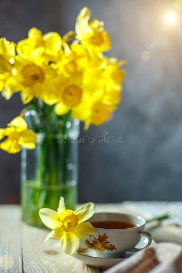黄色黄水仙花束在花瓶和一杯茶在桌上的在早晨静物画 免版税库存图片