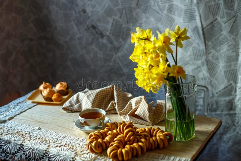 黄色黄水仙花束在花瓶和一杯茶在桌上的在早晨静物画 库存图片