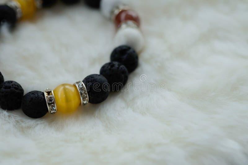 黄色Chrysoberyl猫` s眼睛石头和熔岩石头 运气时运有黄色和黑口气的石头镯子在白色羊毛背景 免版税图库摄影