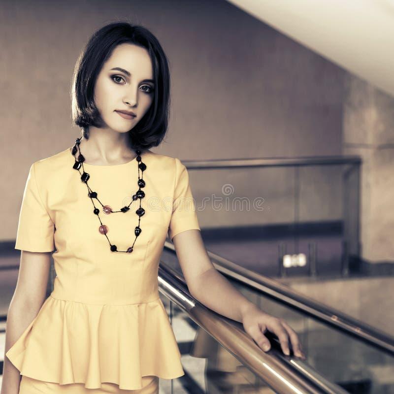 黄色peplum礼服的年轻时装业妇女在办公室 库存图片