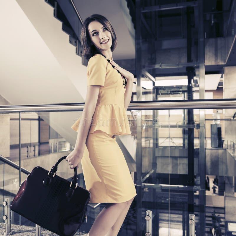 黄色peplum礼服的年轻时装业妇女有提包的在办公室 库存照片