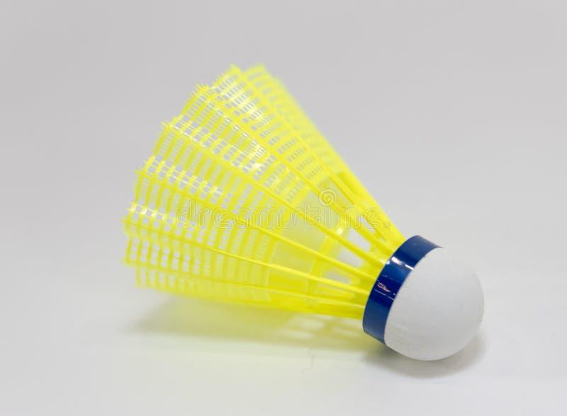 黄色shuttlecock或羽毛球球在与拷贝空间的白色背景中 免版税库存图片