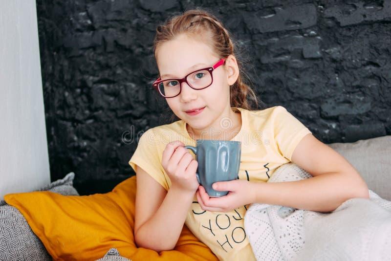 黄色T恤杉的逗人喜爱的非离子活性剂女孩有杯子的tes在床,舒适家上 免版税库存图片