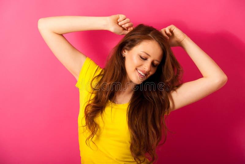 黄色T恤杉舞蹈的美丽的少妇在桃红色 免版税库存照片