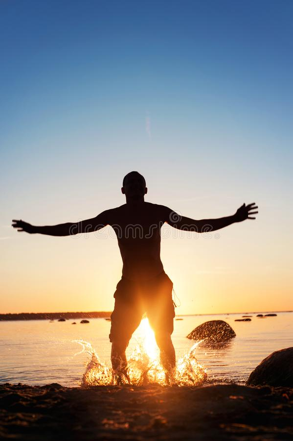 黄金时节夏天 跳跃在水中的愉快的年轻人 库存照片