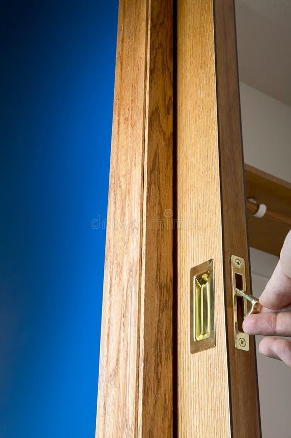 黄铜把柄和边缘在一个木口袋门拉扯 免版税库存图片