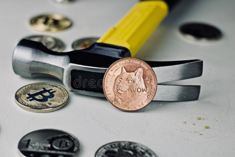 黄铜dogecoin硬币和锤子 免版税库存图片