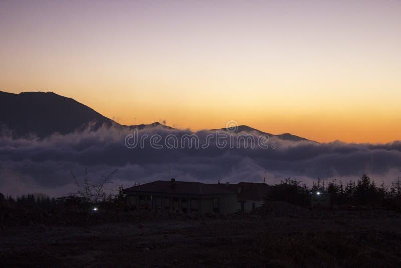 黎巴嫩的风景日落的 在云彩上的议院在山 黎巴嫩 免版税库存照片