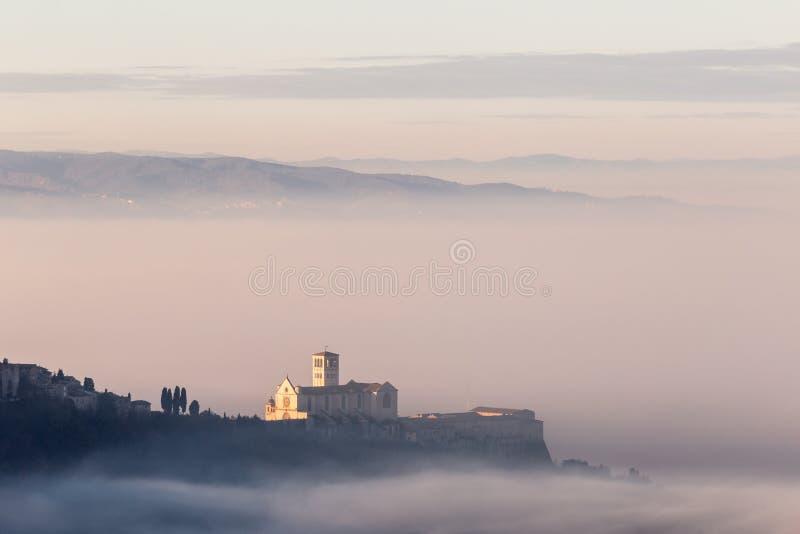 黎明时分雾海上的阿西西镇圣弗朗西斯教堂的壮丽景色 免版税库存照片