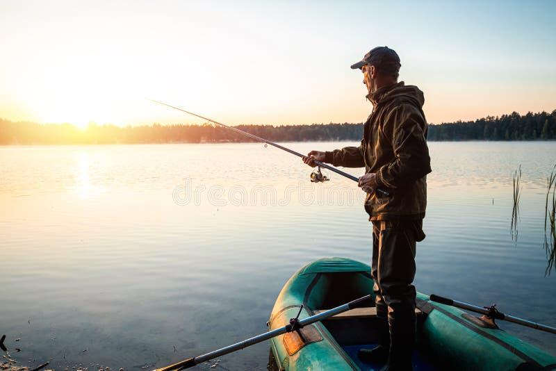 黎明时分,湖上男渔夫钓到钓竿 钓鱼爱好度假概念 复制空间 免版税库存图片