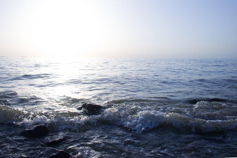 黎明看法在与清楚的天空的海边 海浪波浪和大冰砾石头 与拷贝空间的蓝色背景 免版税库存照片