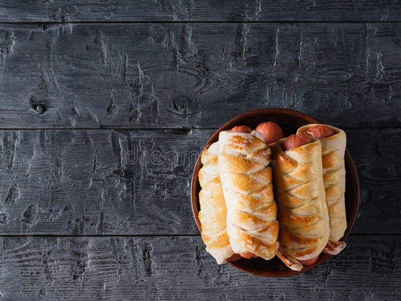 黏土板材充满在一张黑暗的木桌上的新近地煮熟的自创腊肠卷 顶视图 库存图片