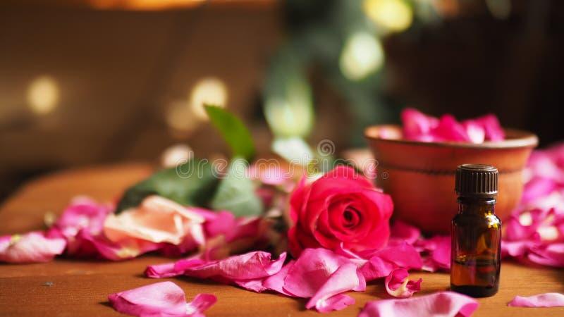 黏土碗和芳香油在玫瑰花瓣在木桌上,自然原料,选择的焦点中的墨镜瓶 免版税图库摄影