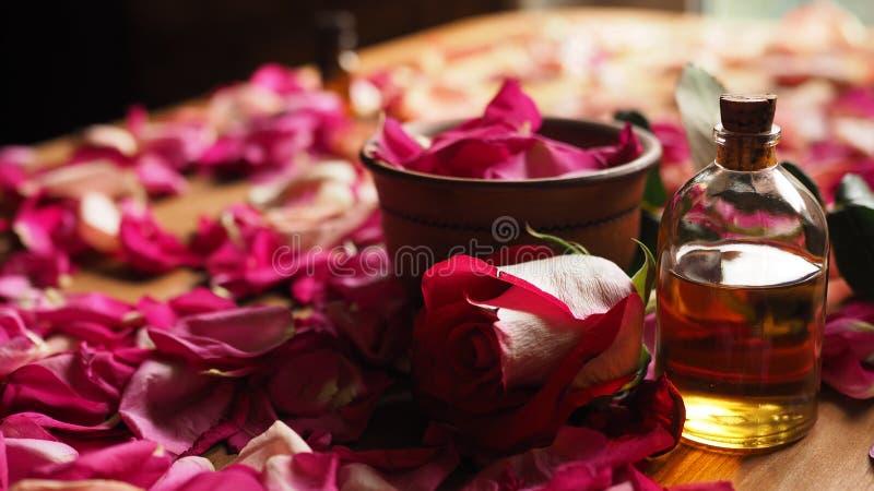 黏土碗和芳香油在玫瑰花瓣在木桌上,自然原料,选择的焦点中的玻璃瓶 库存照片