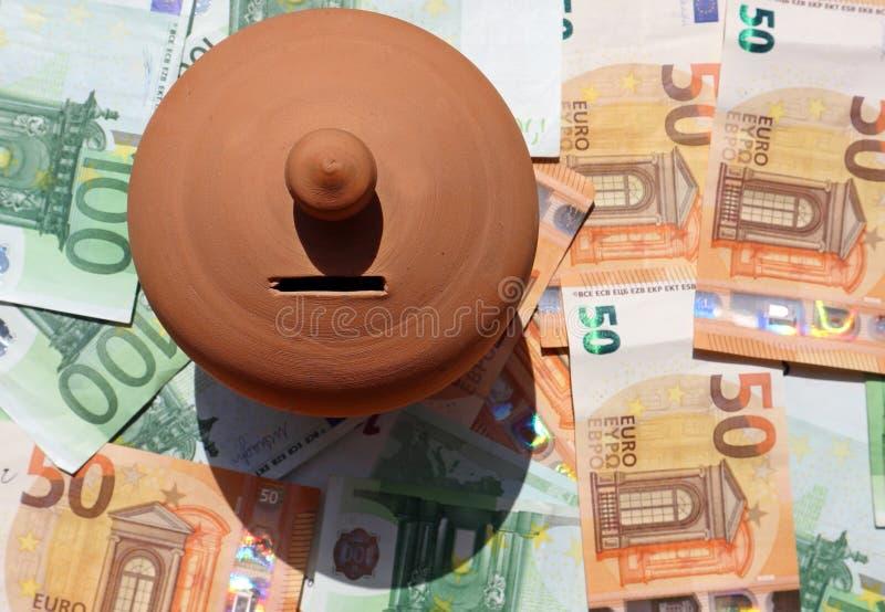 黏土节约金钱箱子或者存钱罐,在疏散的欧元钞票床上  图库摄影
