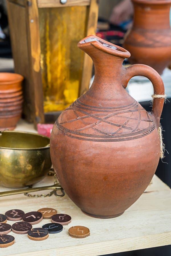 黏土酒水罐几何样式堆硬币大奖章古代北欧文字的样式标签碗金属标度上 免版税库存图片
